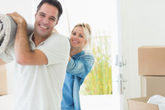 Couple carrying rolled rug after moving in a house Stock Photo