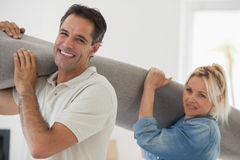 Couple carrying rolled rug after moving in a house Stock Image