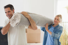 Couple carrying rolled rug after moving in a house. Portrait of a smiling couple carrying rolled rug after moving in a house Royalty Free Stock Photos