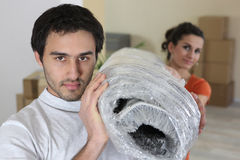 Couple carrying a rug Royalty Free Stock Images