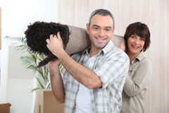 Couple carrying rug Stock Images