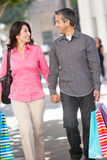 Couple Carrying Shopping Bags On City Street Stock Photography