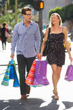 Couple Carrying Shopping Bags On City Street Stock Image