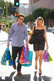 Couple Carrying Shopping Bags On City Street Stock Images