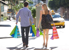 Couple Carrying Shopping Bags On City Street Royalty Free Stock Photography
