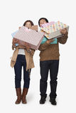 Couple carrying shopping bags, studio shot Stock Images