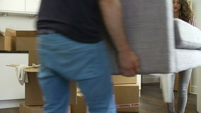 Couple Carrying Sofa As They Move Into New Home stock video