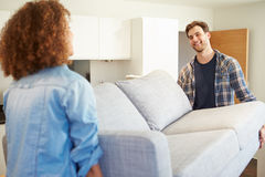 Couple Carrying Sofa As They Move Into New Home Royalty Free Stock Image