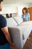 Couple Carrying Sofa As They Move Into New Home. Smiling At Each Other royalty free stock images