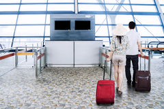 Couple carrying suitcases in the airport terminal Royalty Free Stock Image