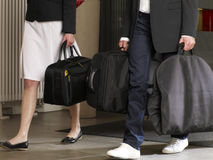 Couple carrying their luggage in a hotel. Royalty Free Stock Photography