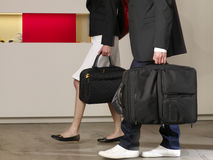 Couple carrying their luggage in a hotel. Stock Images