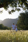 Couple carrying wine and holding hands near table in rural field Stock Photos