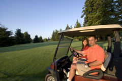 Couple in Cart on Golf Course - Horizontal. A young couple is riding in a golf cart on a golf course.  They are smiling at the camera.  Horizontally framed shot Royalty Free Stock Photography