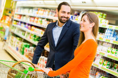 Couple with cart grocery shopping in shop Royalty Free Stock Images