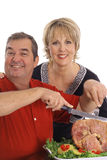 Couple carving a ham Royalty Free Stock Photos
