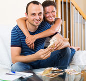 Couple with cash at home Royalty Free Stock Photos