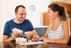 Couple with cash at home Stock Photography