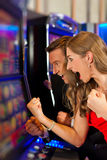 Couple in Casino. On a slot machine winning and having fun Stock Image