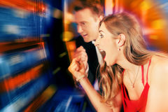 Couple in Casino on slot machine. Gambling couple in Casino or amusement arcade on slot machine winning Stock Photo