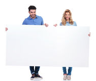 Couple of casual people presenting a big blank billboard. On white background royalty free stock image
