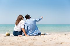 Couple in casual sitting on the sand at the beach royalty free stock photos