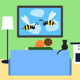 Couple and cat watching television sitting on couch in room. Stock Photos