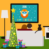 Couple and cat watching television sitting on the couch in the room Royalty Free Stock Photos