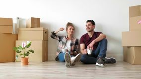 Couple catching a break while moving house. Young couple catching a break while moving house stock video footage