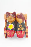 A Couple of Cats in Love. Wooden statuette of cats sitting on a bench and kissing Royalty Free Stock Photos