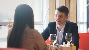 Couple celebrate Valentine`s day with romantic dinner in restaurant. Young happy couple romantic date drink glass of white wine at restaurant stock footage