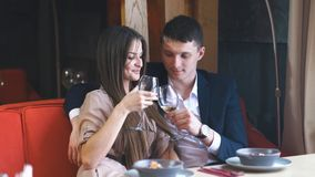 Couple celebrate Valentine`s day with romantic dinner in restaurant. Young happy couple romantic date drink glass of white wine at restaurant stock video footage