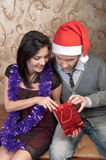 A couple celebrates Christmas. Young and beautiful couple exchanged Christmas gifts Royalty Free Stock Photo