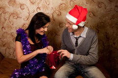 A couple celebrates Christmas. Young and beautiful couple exchanged Christmas gifts Stock Photography