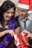 A couple celebrates Christmas. Young and beautiful couple exchanged Christmas gifts Royalty Free Stock Images
