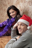 A couple celebrates Christmas. Young and beautiful couple exchanged Christmas gifts Stock Images