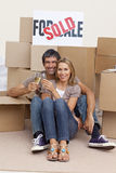 Couple celebrating with champagne a new house Stock Image