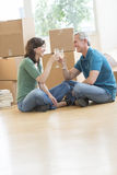 Couple Celebrating With Champagne In New House. Happy mature couple celebrating with champagne against cardboard boxes in new house Stock Photography