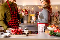 Couple celebrating Christmas in the kitchen and drink wine royalty free stock image