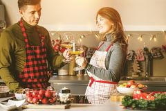 Couple celebrating Christmas in the kitchen and drink wine stock photo