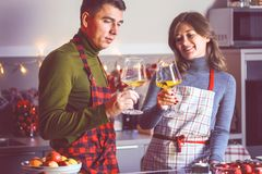 Couple celebrating Christmas in the kitchen and drink wine stock photography