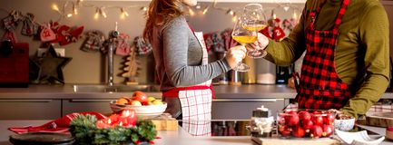 Couple celebrating Christmas in the kitchen and drink wine royalty free stock photo