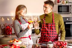 Couple celebrating Christmas in the kitchen and drink wine stock image