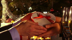 Couple celebrating Christmas - Male hands give over a gift looking like a heart stock footage