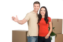 Couple celebrating new home with keys and moving boxes. Royalty Free Stock Image