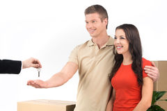 Couple celebrating new home taking keys and moving boxes. Stock Images