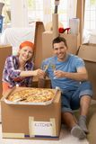 Couple celebrating new house with champagne. Happy couple celebrating new house with pizza and champagne at lunch break of moving stock photos