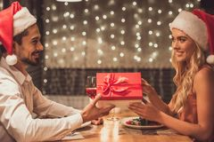 Couple celebrating New Year. Beautiful young couple in Santa hats is looking at each other, holding a gift box and smiling while celebrating New Year in a Stock Images