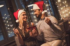 Couple celebrating New Year. Beautiful young couple in Santa hats is looking at each other, holding sparklers, drinking wine and smiling while celebrating New Royalty Free Stock Images