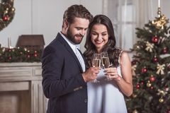 Couple celebrating New Year. Merry Christmas and Happy New Year! Cheerful and elegant couple is clinking glasses of champagne together and smiling while Stock Photo
